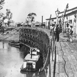 Echuca Wharf with several men standing near a loading crane